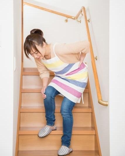 腰の痛みを我慢する女性